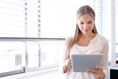 Buy stock photo Lovely young woman working on a digital tablet - copyspace