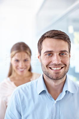 Buy stock photo Handsome young businessman smiling at the camera with his female colleague in the background - portrait