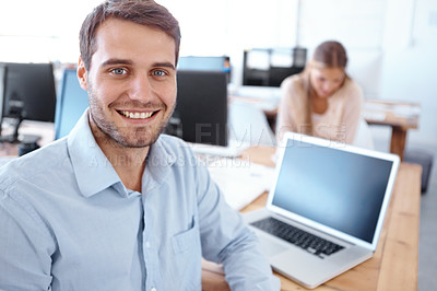 Buy stock photo Handsome young businessman sitting at his desk with his co-worker in the background