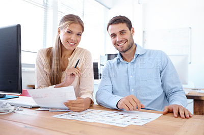 Buy stock photo Two business colleagues sitting at a desk with paperwork in front of them - portrait