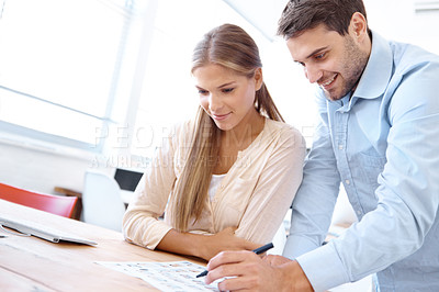 Buy stock photo Young businessman leaning over his colleagues shoulder and writing something on a document