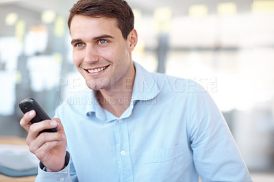 Buy stock photo Handsome young businessman smiling while sending a text - copyspace