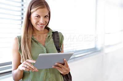 Buy stock photo Lovely young student holding a digital tablet and smiling at the camera