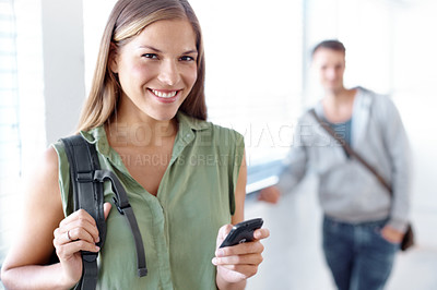 Buy stock photo Pretty young student texting on her cellphone with her male friend in the background