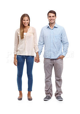 Buy stock photo Happy young couple holding hands and smiling at the camera
