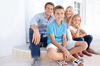 Buy stock photo A happy family of four sitting on their doorstep together