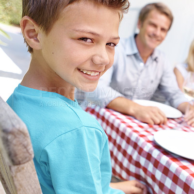 Buy stock photo A young boy looking over his shoulder while enjoying lunch with his family