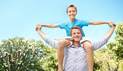 Buy stock photo A young boy sitting on his father's shoulders on a bright summer's day