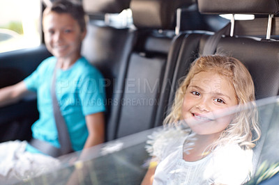 Buy stock photo A cute young girl sitting in the backseat of the car with her brother