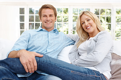 Buy stock photo A comfortable mature couple sitting on their lounge couch together