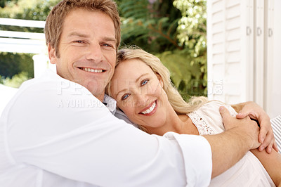 Buy stock photo A happy mature couple hugging each other outdoors on a bright summer's day