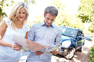 Buy stock photo A lost couple standing outside their car looking at a map with copyspace