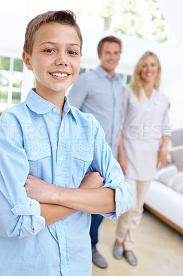 Buy stock photo Portrait of a boy smiling with his arms crossed with his mother and father blurred in the background