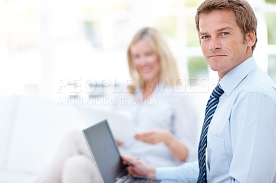 Buy stock photo Portrait of a smiling business man with a laptop on his lap and a blurred woman in the background and copyspace