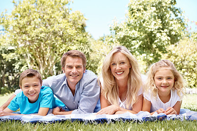 Buy stock photo Happy family lying on a blanket together in the park