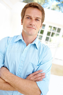 Buy stock photo Composed and handsome mature man standing with his arms folded