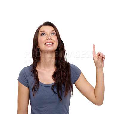 Buy stock photo Smiling young woman pointing upwards against a white background