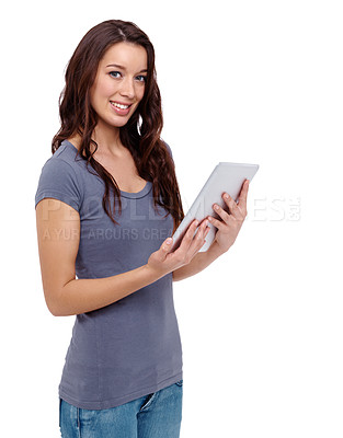 Buy stock photo Attractive young woman using a digital tablet while standing against a white background