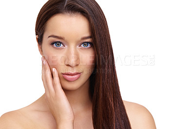 Buy stock photo Cropped view of a beautiful young woman with long brown hair and flawless skin looking at you against a white background while touching her face