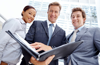 Buy stock photo Low view of a business team looking over their notes together