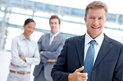 Buy stock photo A business manager standing with his team blurred in the background