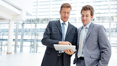 Buy stock photo Two business associates working on a digital tablet together