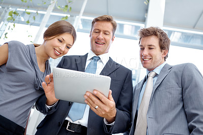 Buy stock photo Three business associates working on a digital tablet together