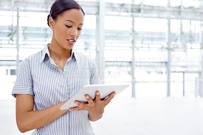 Buy stock photo A pretty businesswoman working on her digital tablet at the office