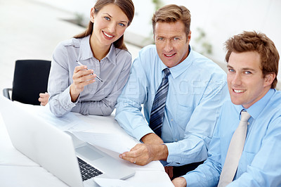 Buy stock photo A team of businesspeople working on a laptop together