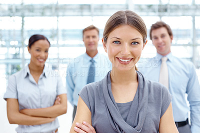 Buy stock photo A gorgeous young businesswoman smiling at the camera with her colleagues in the background