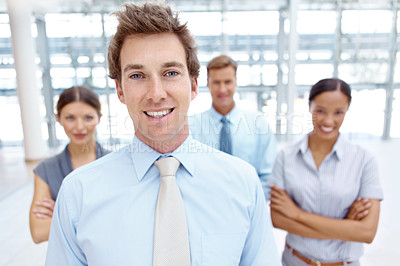 Buy stock photo A handsome young businessman smiling at the camera with his colleagues in the background