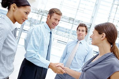 Buy stock photo A businessman greeting a colleague with a handshake