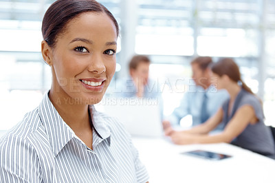 Buy stock photo Closeup of a beautiful young businesswoman smiling at the camera with her colleagues in the background