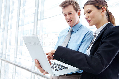 Buy stock photo A handsome young buisnessman and his co-worker working together on a laptop