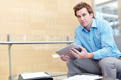 Buy stock photo A handsome young businessman holding a digital tablet while sitting in his office