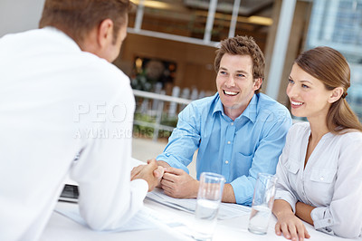 Buy stock photo A happy young couple closing a business deal