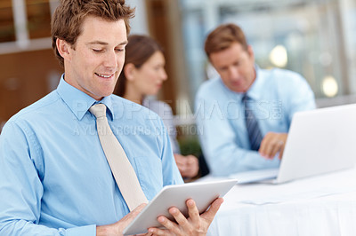 Buy stock photo Closeup of a young businessman working on his digital tablet with his colleagues in the background
