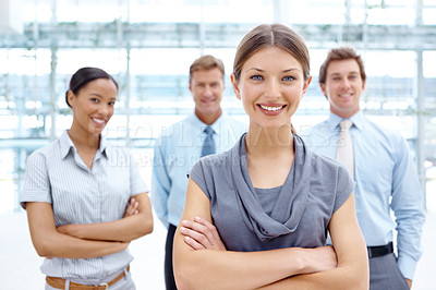 Buy stock photo Beautiful young businesswoman standing and smiling with her arms folded and her colleagues in the background