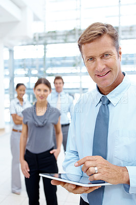 Buy stock photo Mature businessman using his tablet with a smile while his team stands in the background