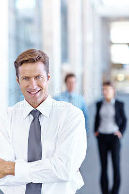 Buy stock photo Handsome mature businessman smiling with coworkers in the background