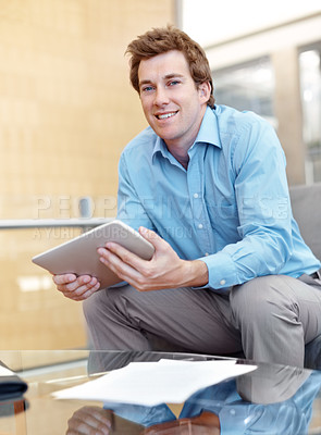 Buy stock photo Young businessman using a tablet while smiling