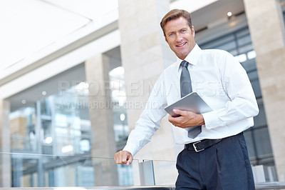 Buy stock photo Handsome mature businessman holding a digital tablet while standing indoors