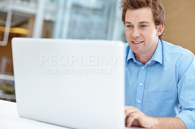 Buy stock photo Young businessman using a laptop while sitting indoors