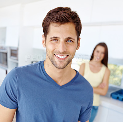 Buy stock photo Portrait of a smiling handsome man folding his arms with his girlfriend in the background