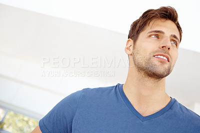 Buy stock photo Low angle close up shot of a handsome young man standing in a living room
