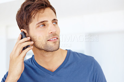 Buy stock photo Close up shot of a handsome young man talking on a cellphone inside