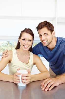 Buy stock photo Portrait of a good-looking young couple sitting at a counter in their kitchen