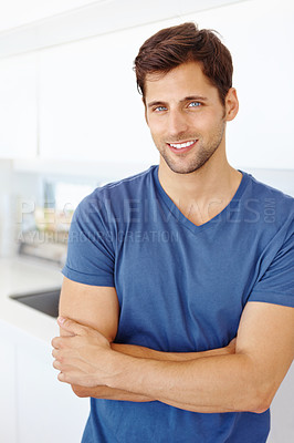 Buy stock photo Portrait of a handsome young man standing in his kitchen with his arms folded
