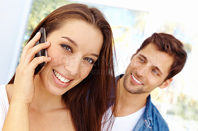 Buy stock photo Close up portrait of an attractive young woman talking on a cellphone with her husband standing in the background