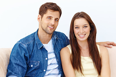 Buy stock photo Portrait of a happy-looking young couple sitting on a sofa in their living room